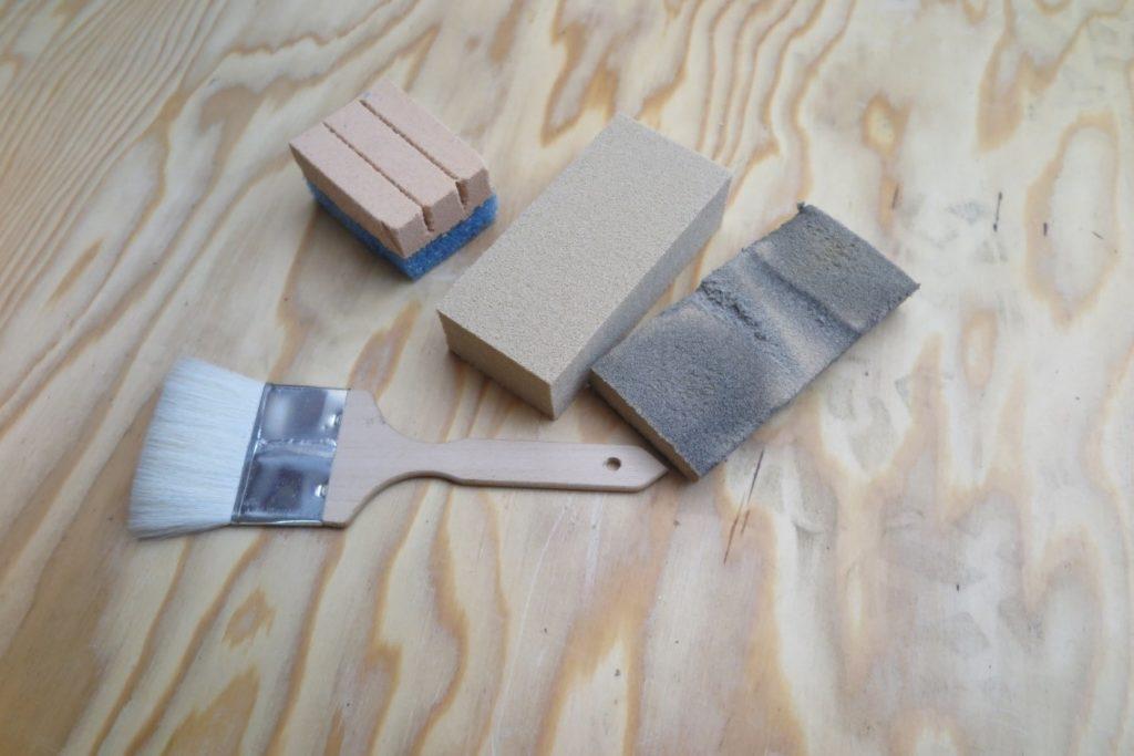 Materialer til tørrensning: gedehårspensel, Akapad tørsvamp (den orange) og Sodsvamp, før og efter brug.