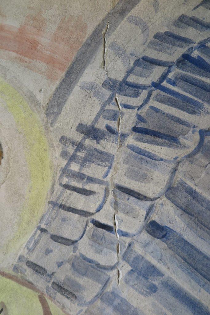 Revne gennem englevinge i nordre sideskibs 6. fag. Motivet befinder sig over norddøren, og revnen skyldes sandsynligvis mange års rystelser i murværet, når døren åbnes og lukkes.