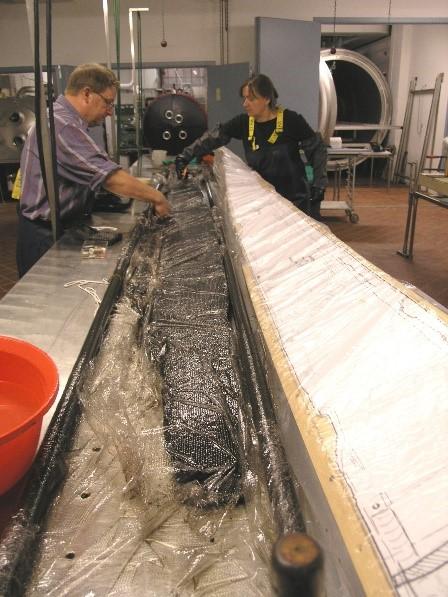 En af Gislingebådens planker gøres parat til at blive lagt i facon før frysetørring, på en træplade formet efter rekonstruktionen af båden. Foto: Nationalmuseet, Anne Moesgaard.