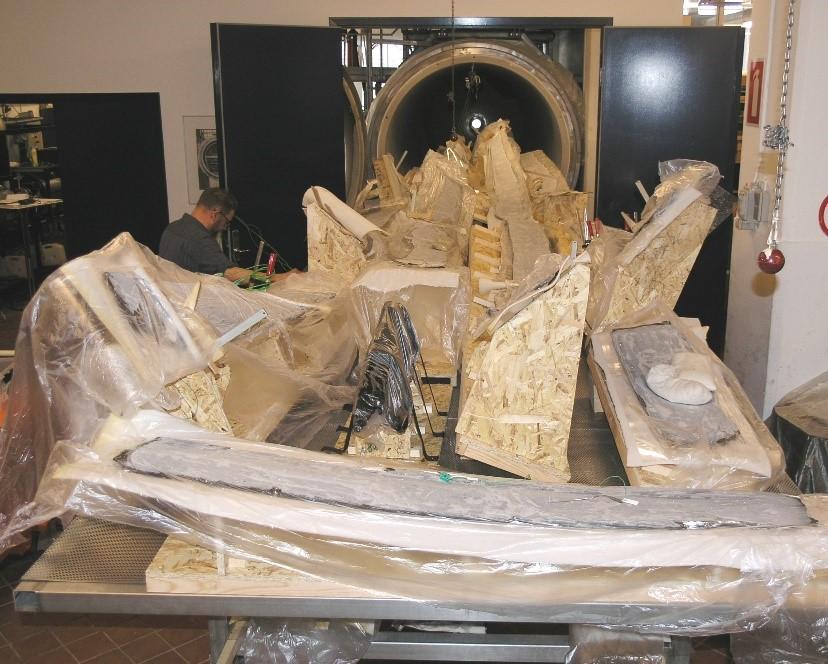 Plankerne ligger i facon på frysetørrerens slæde parat til at blive rullet ind i fryseren. Træet er dækket med plastik, for at væsken ikke skal fordampe fra træet, inden det bliver frosset ind under frysetørringsprocessen. Foto: Nationalmuseet, Anne Moesgaard.