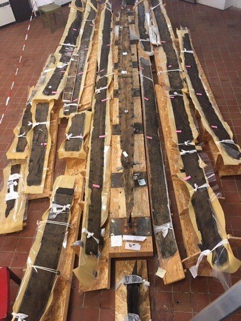 Plankerne, der stadig ligger på deres understøtninger fra frysetørringen, er her lagt op, så vi kan forestille os, hvilken rækkefølge de skal ligge i. Kølen ses lige i midten. Foto: Nationalmuseet, Anette Hjelm Petersen.