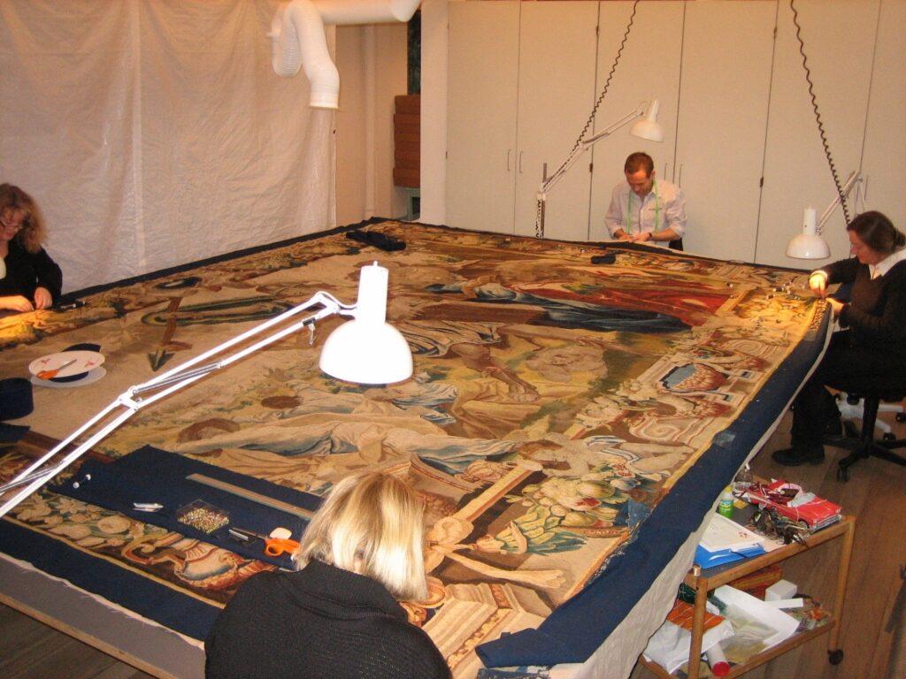 Montering af blå kant og velcrobånd til ophæng. Foto: Nationalmuseet, Marie-Louise Jacobsen